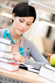 Attractive woman reads at the library — Stock Photo