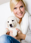 Woman with white puppy on her knees — Stock Photo