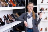 Woman with shoe in hand chooses stylish pumps — Stock Photo
