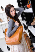 Woman choosing a pair of shoes in shop — Stock Photo