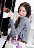 Woman choosing a pair of footwear in shop — Stock Photo