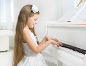 Profile of little girl in white dress playing piano — Stock Photo