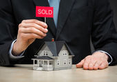 Little house and hand keeping sold tablet — Stock Photo