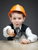 Little boy in headpiece with house model and ruler — Stock Photo