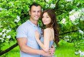 Couple embracing near blossomed tree — Stock Photo