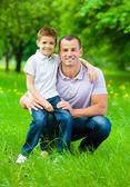 Pai mantém filho no joelho — Fotografia Stock
