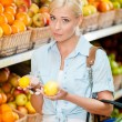 Girl at the market choosing fruits hands lemons — Stock Photo #36980653