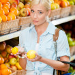 Girl at the market choosing fruits hands lemons — Stock Photo