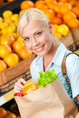Girl holds paper bag with fresh vegetables — Stock Photo