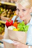 Girl hands packet with fresh vegetables reading list of products — Stock Photo