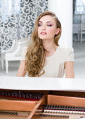 Portrait of female sitting at the piano — Stock Photo