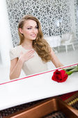 Portrait of woman with scarlet rose playing piano — Stock Photo