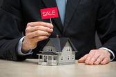 Close up of little home and hand keeping sale tablet — Stock Photo
