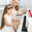 Teacher teaches little girl to play piano — Stock Photo #36991777