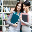 Two girlfriends hug at the library — Stock Photo