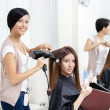 Hairdresser does hair style of woman in hairdressing salon — Stock Photo #39906411