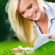 Pretty girl reading book on the grass — Stock Photo