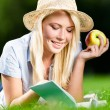 Girl in straw hat with apple reads book on the green grass — Stock Photo #39907145