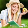 Girl in straw hat with apple reads book on the green grass — Stock Photo