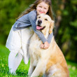 Little girl Little girl embraces golden retriever in the park — Stock Photo