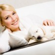 Woman sitting on the sofa with sleeping puppy — Stock Photo