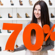 Woman keeps the model of 70 percentage sale on shoes — Stock Photo #39908485