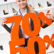 Woman showing the percentage of sales on high heeled shoes — Stock Photo #39908567