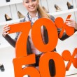 Woman showing the percentage of sales on high heeled shoes — Stock Photo