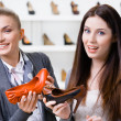 Stock Photo: Salesperson offers high heeled shoes for customer