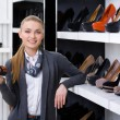 Woman with shoe in hand chooses high heeled shoes — Stock Photo #39908765