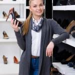 femme avec chaussure en main choisit pompes — Photo #39908851