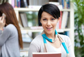 Young woman student at the library against bookshelves — Stock Photo