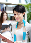 Young female student at the library against bookshelves — Stock Photo
