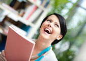 Student with book at the library — Stock Photo