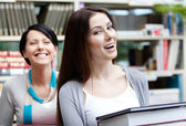 Two laughing girlfriends carry books — Stock Photo