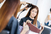 Reflection of beautician doing haircut for woman — Stockfoto