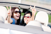 Two girls sitting in the car and gesturing victory sign — Stock Photo
