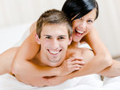 Close up of laughing couple who plays in bed — Stock Photo