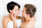 Close up of man stroking woman lying in bed — Stock Photo