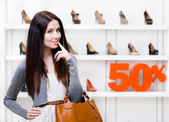 Portrait of female in shop with 50 percentage sale — Stock Photo