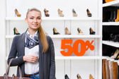 Portrait of lady in shop with 50 percentage sale — Stock Photo