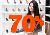 Woman keeps the model of 70 percentage sale on shoes — Stock Photo