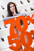 Woman showing the percentage of sales on footwear — Stock fotografie