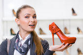 Woman keeping orange leather pump — Stock Photo
