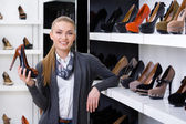 Woman with shoe in hand chooses high heeled shoes — Stock Photo