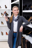 Woman with shoe in hand chooses pumps — Stock Photo