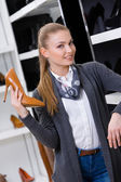 Woman with shoe in hand chooses footwear — Stock Photo