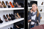 Woman looking at the rows of footwear — Stock Photo