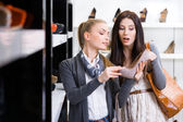 Salesperson shows heeled shoes to the customer — Stock Photo