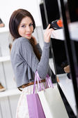 Woman choosing a pair of pumps in shop — Stock Photo